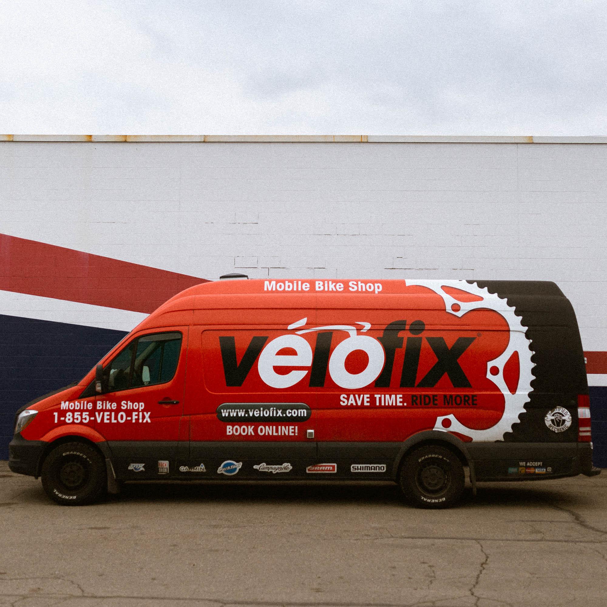 A side-shot of a mobile van bike repair shop.
