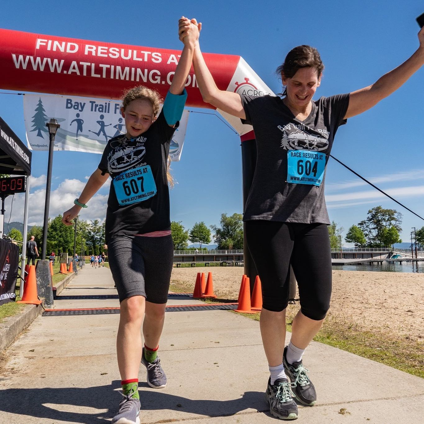 A mother and daughter crossing the finish line of a fun run.