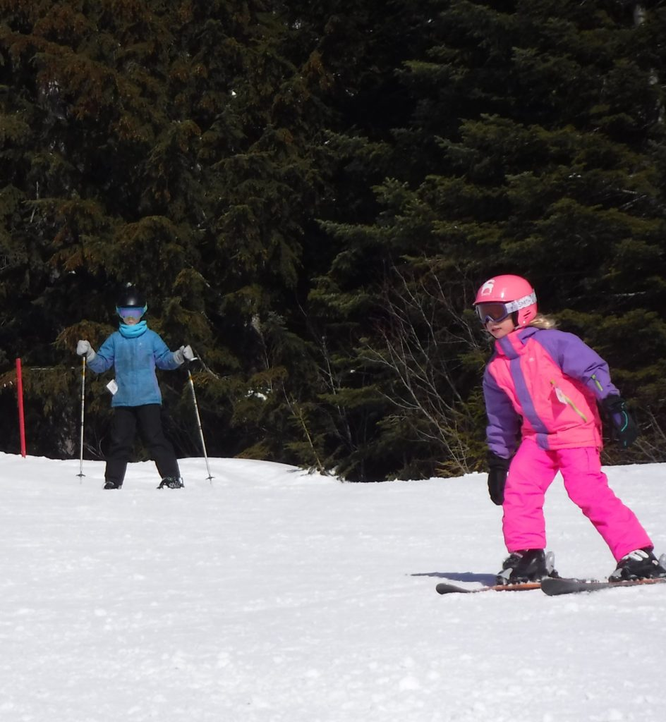 Young girls skiing down the bunny hill run at Schweitzer.