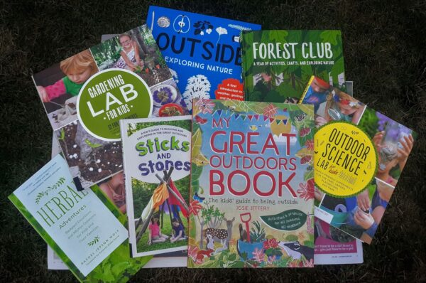 Various nature books for kids, that provide activities and ideas for learning about science, nature, art, and more -- displayed on the grass with their covers showing.