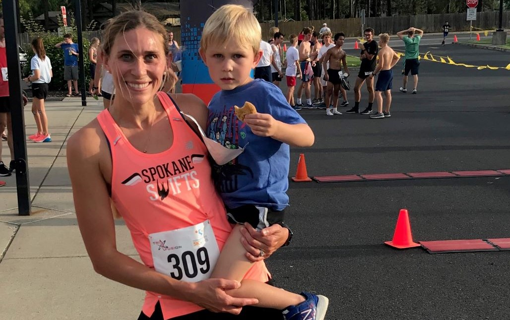 A woman holding her son after finishing a marathon.