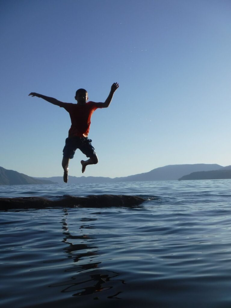 A boy jumping off a dock into a lake.