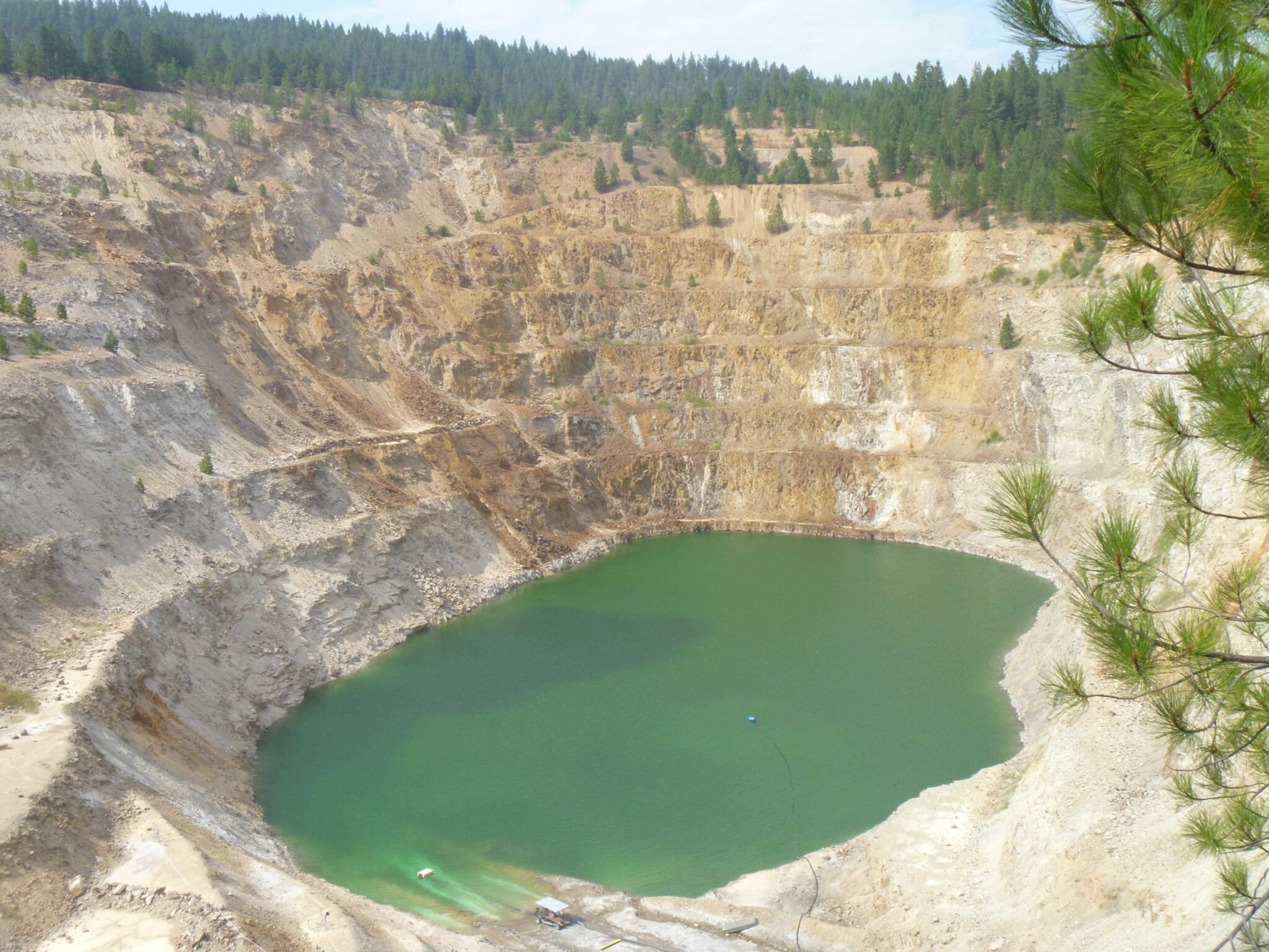 A tan and white mine with green-blue water at the bottom.