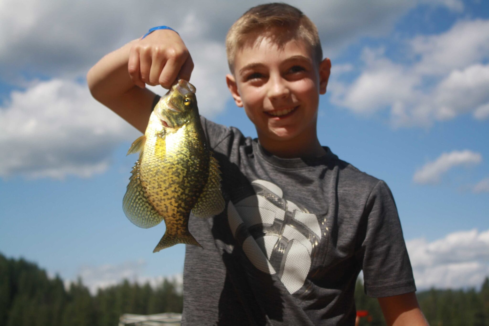 A teen boy holding a fish.