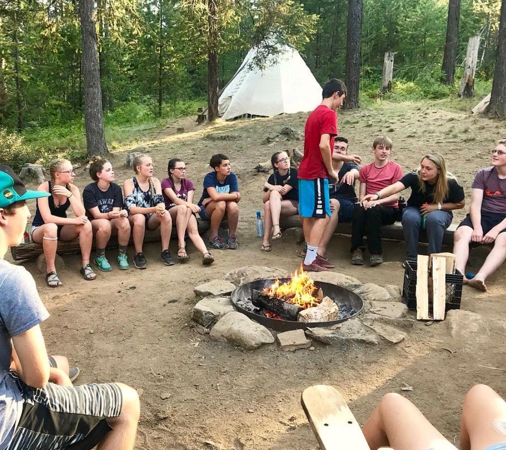 A group of kids around a campfire.