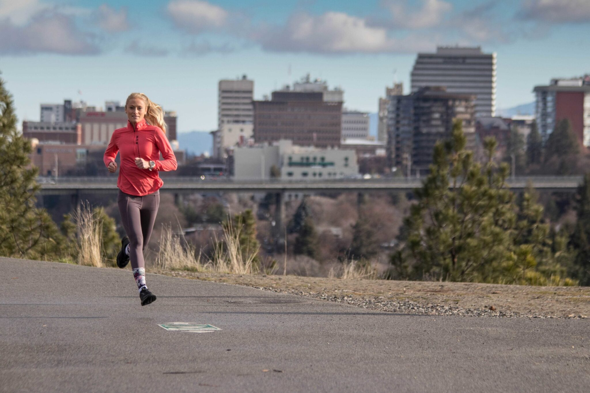 A woman running on a paved trail.