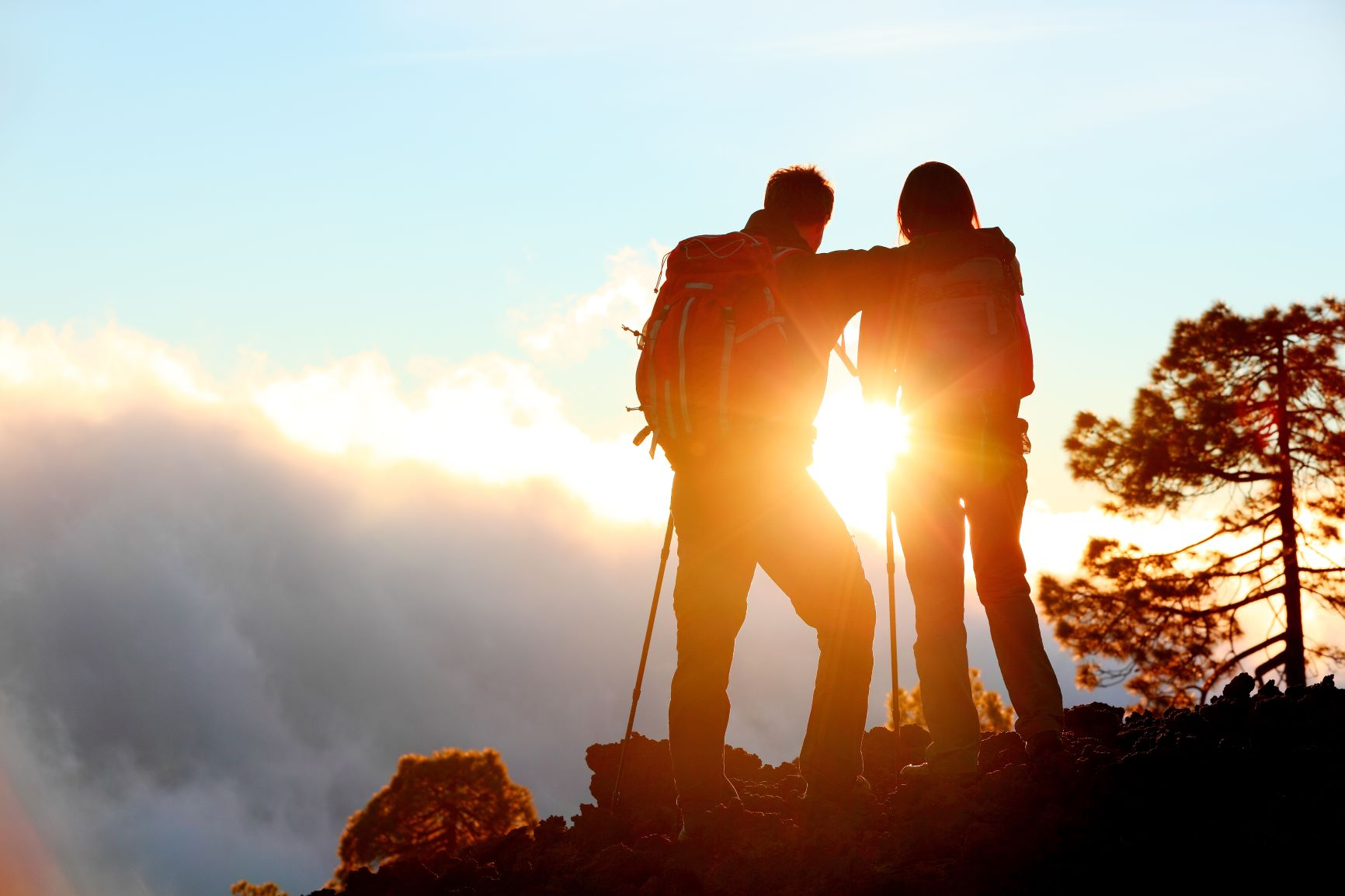 A man and a woman hiking while looking at a sunset.