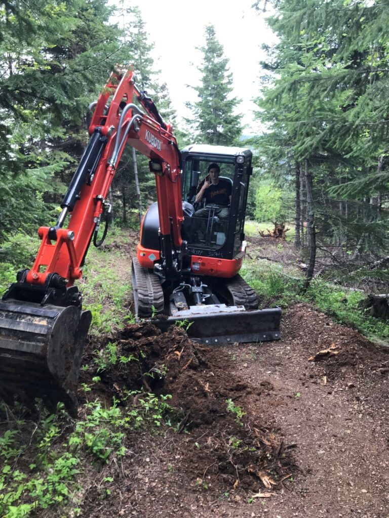 A person in a construction machine, clearing a trail.