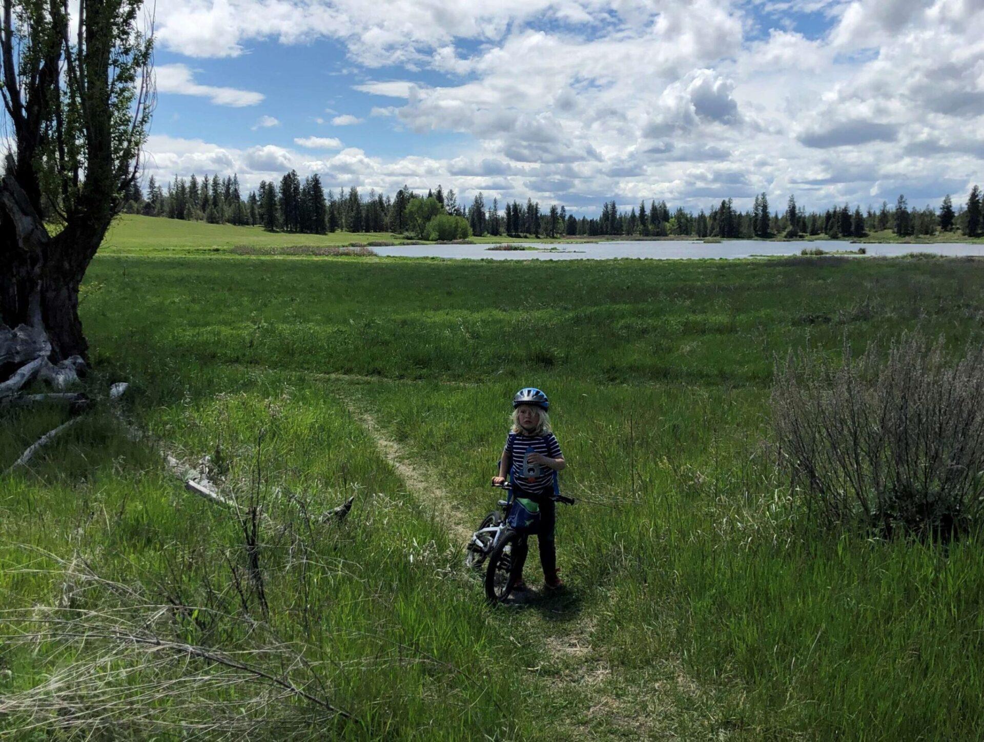 A kid biking along a lake trail.