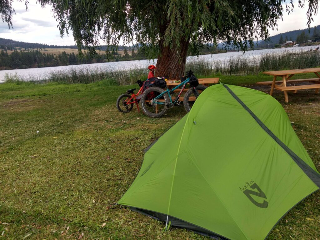 A biking campsite near a lake.