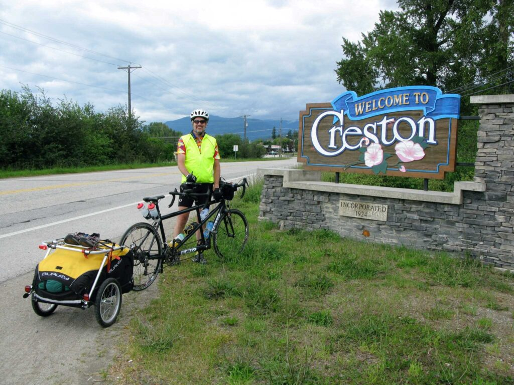 A bike rider taking a break with his gear in front of a town sign.