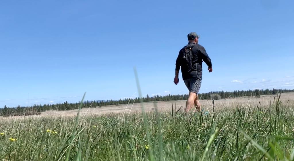 A man walking through a grass field.