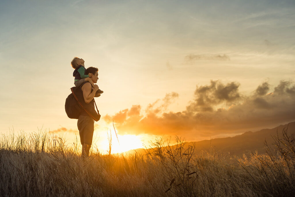 A man holding his kid on his shoulders during a hike.