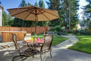 Patio furniture with a manicured lawn behind it.