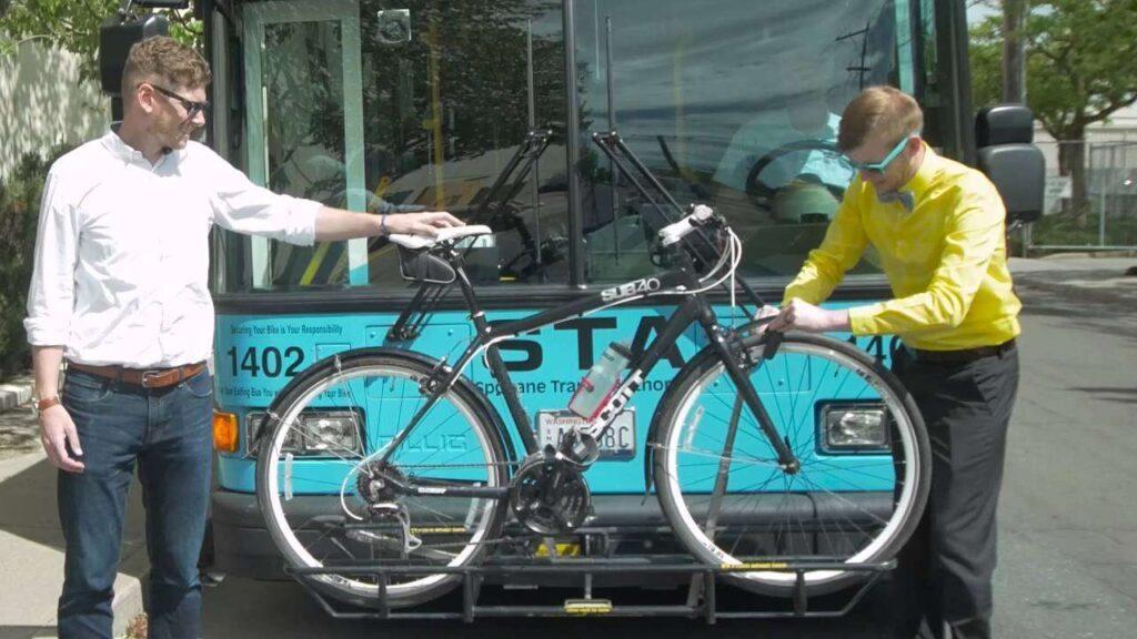 Two guys loading a bike onto a bike rack on a STA bus.