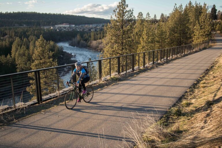 Person biking on the Centennial Trail that runs alongside the Spokane River.