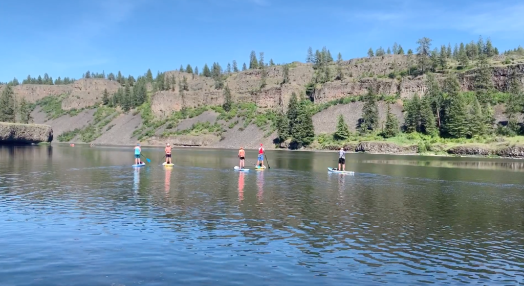 A group of people paddle-boarding on a lake.