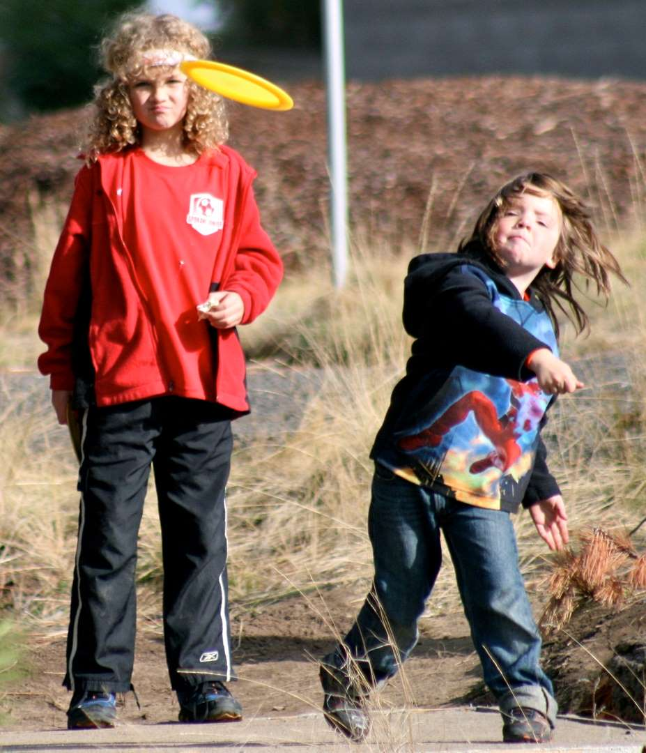 Two kids playing disc golf.