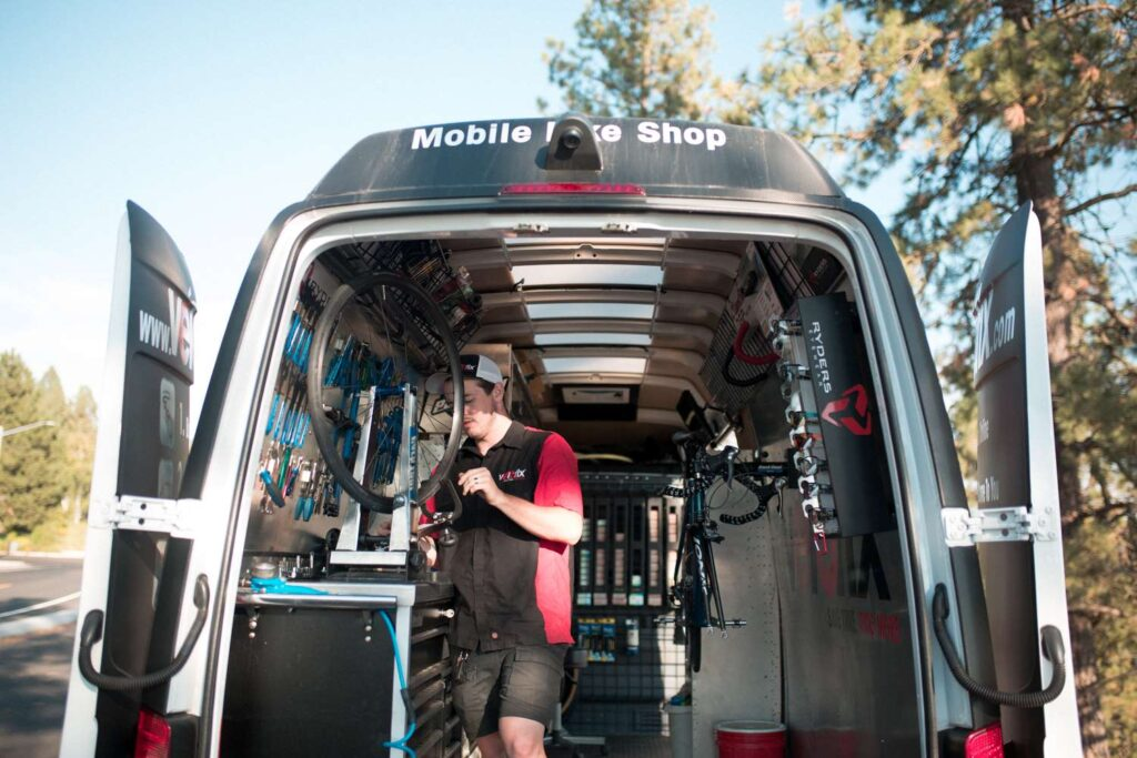 A man fixing a bike in a mobile van bike repair shop.
