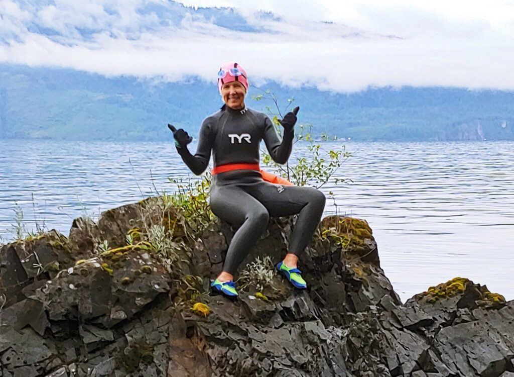 A woman smiling with a wet-suit on.