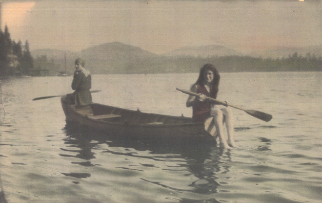 A old black and white vintage photo of two women canoeing.