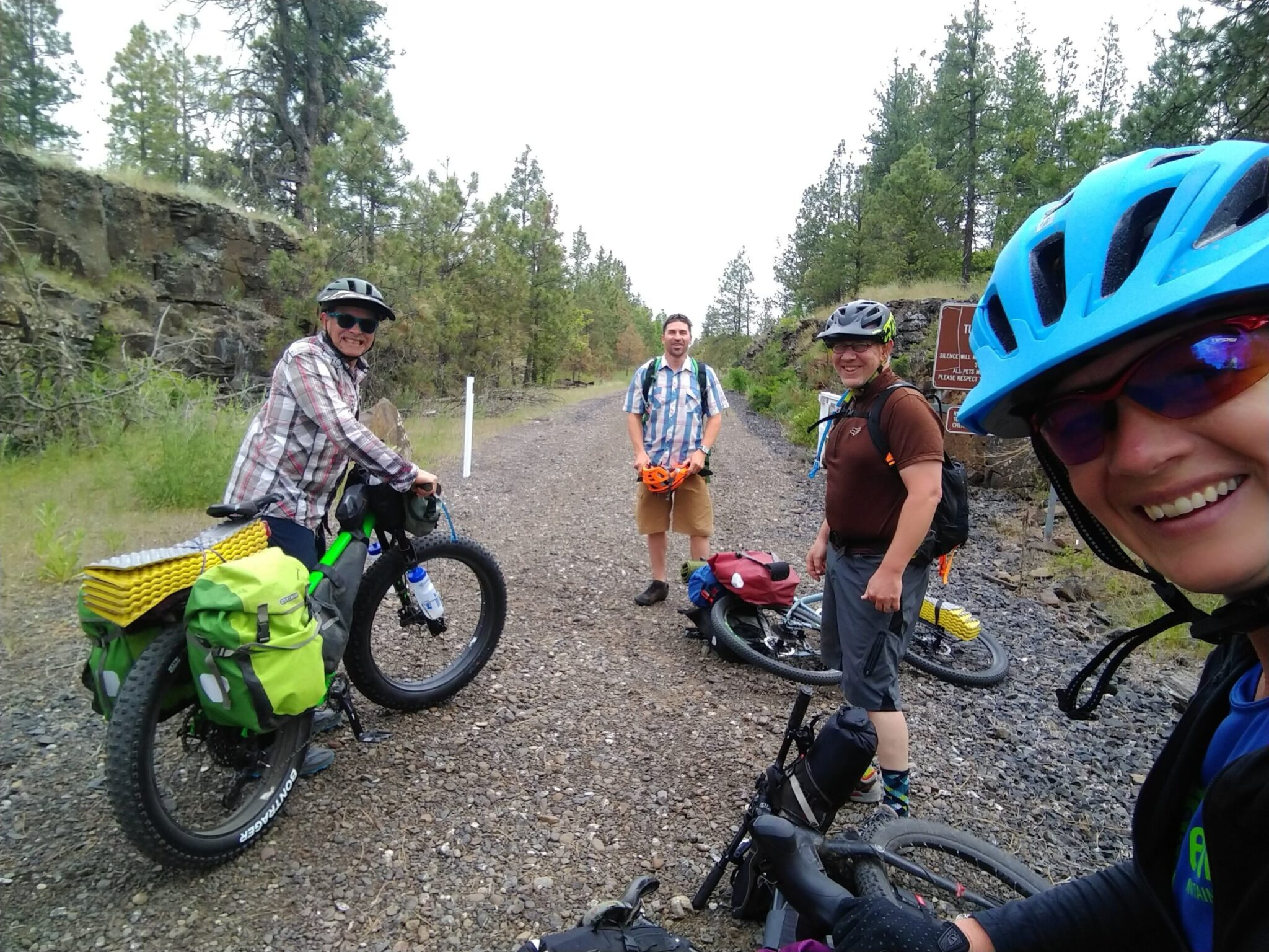 A woman taking a selfie with three other men bike riders.