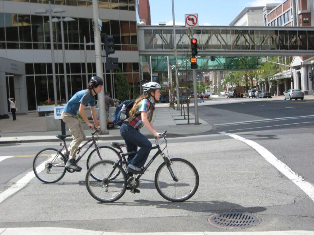 Two people biking downtown.