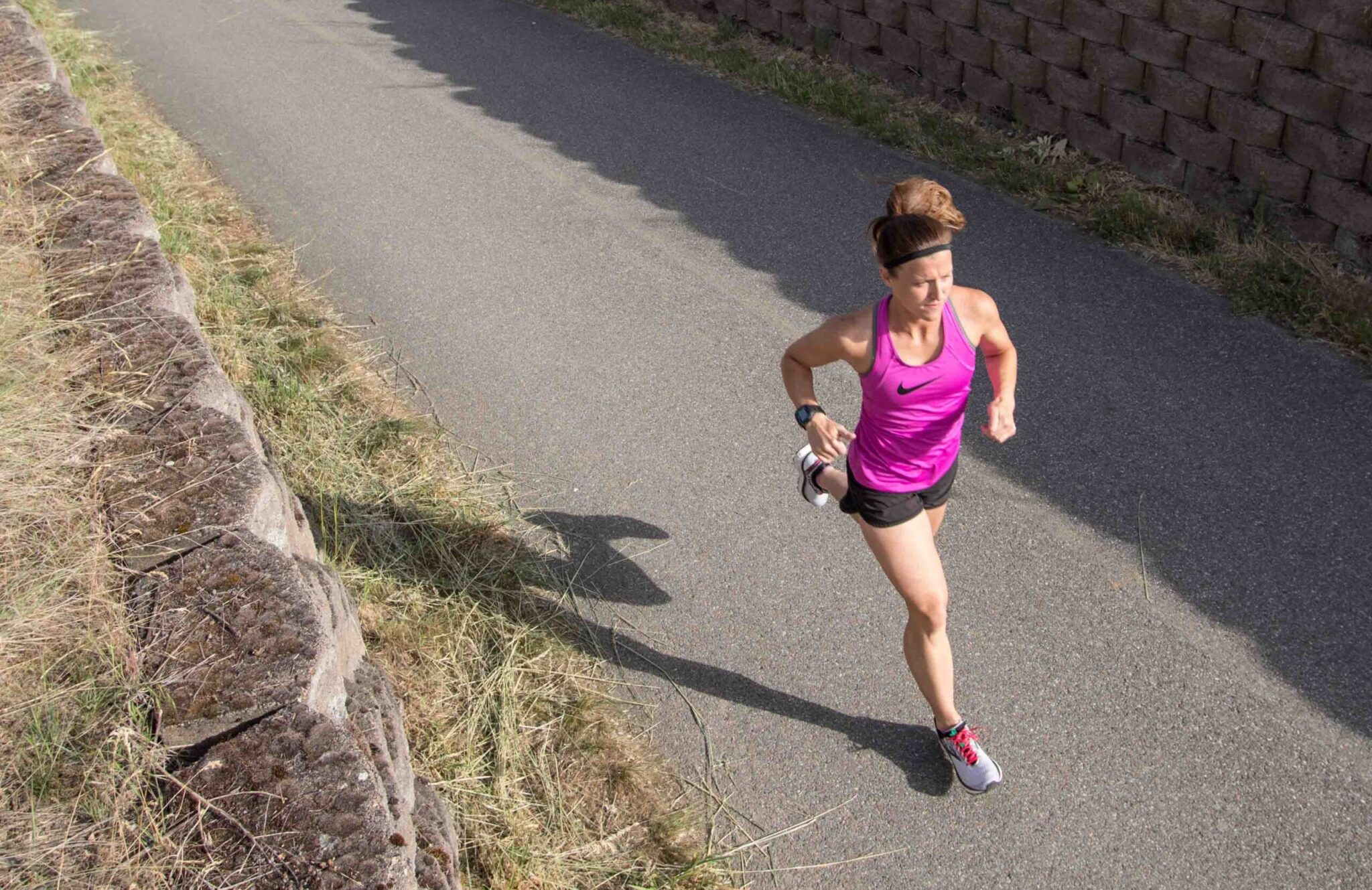Woman with a purple top running on a paved trail.