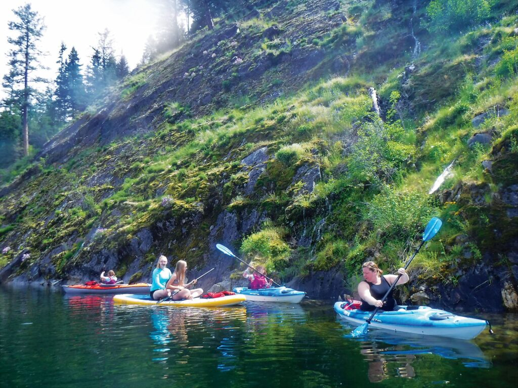 A family of kayakers on Lake Sullivan, along the moss-covered rocky shoreline with a small waterfall.