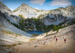 Three people hiking towards a lake.