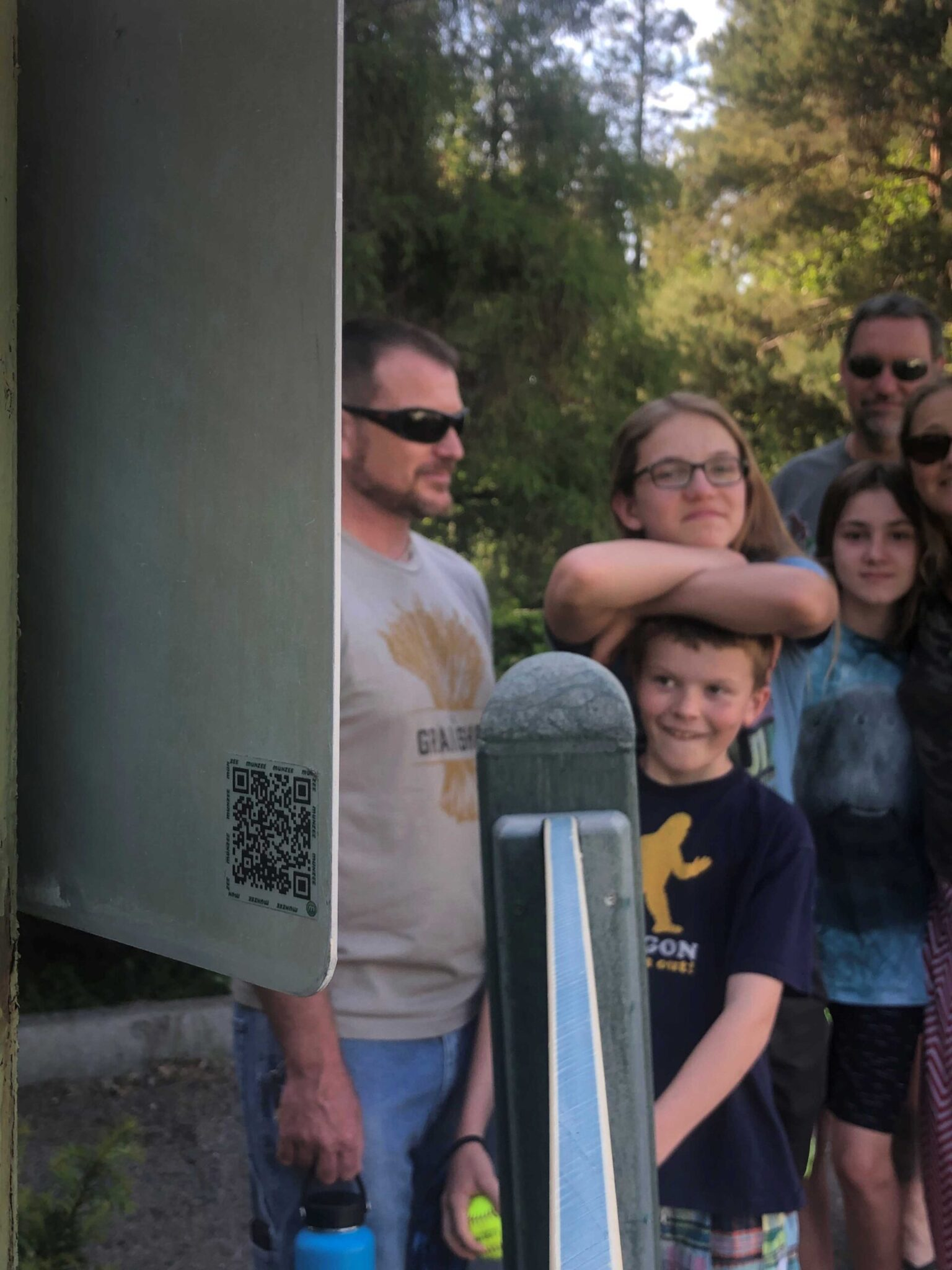A QR code with a family in the background.