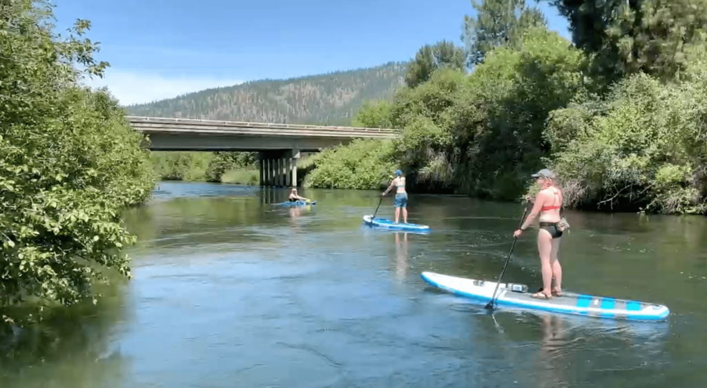 Two people paddle-boarding and one kayaking down a river.