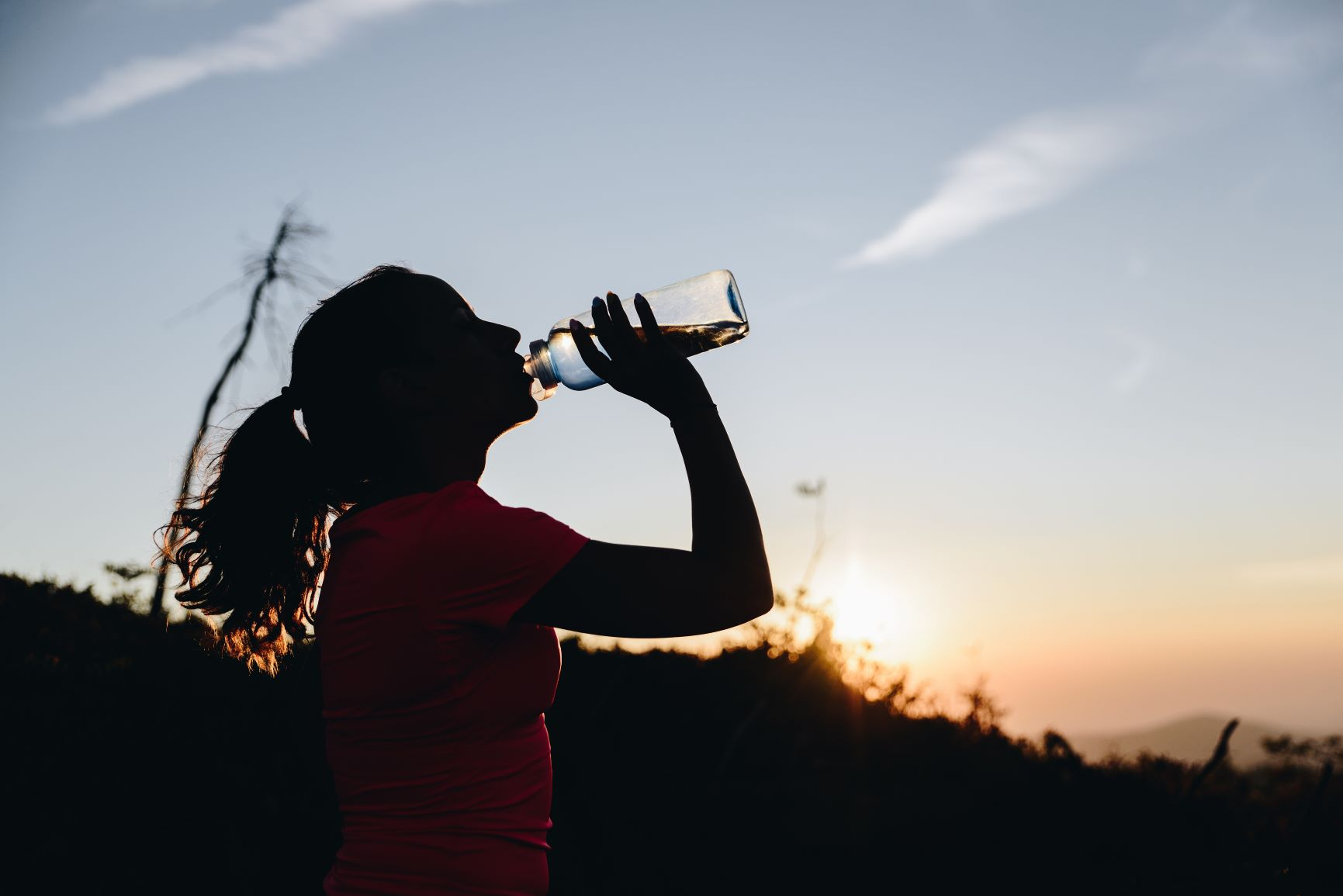Silhouette of a woman drinking water.