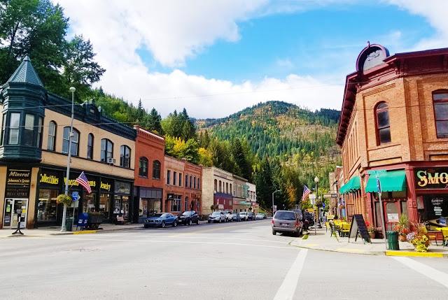 Old buildings on main street with a forested mountain in the background.