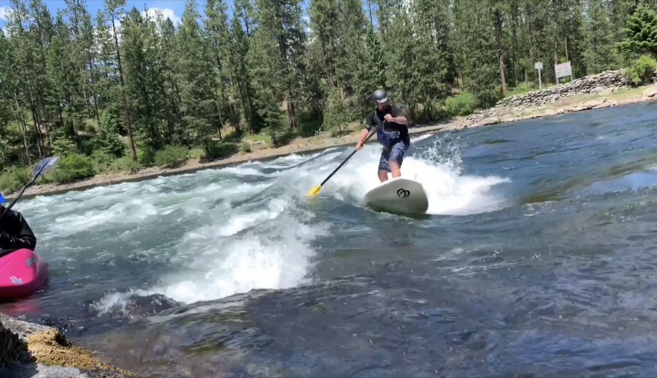 Person paddle-boarding down rapids.