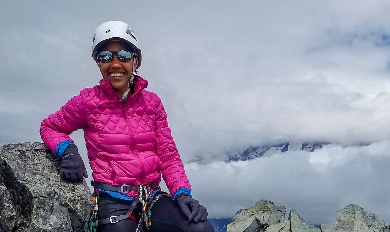 Woman with a pink jacket smiling at the top of a mountain.