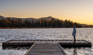 A person on a dock overlooking a lake.
