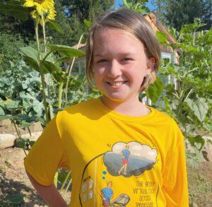 A girl smiling in her garden.