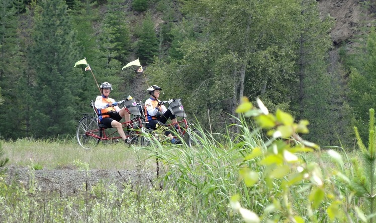 A couple tricycling down a trail.