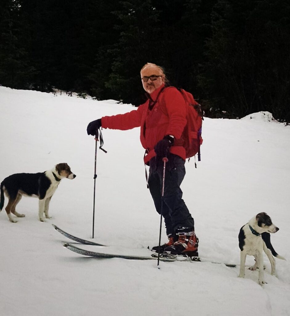 A man skiing with his two dogs.