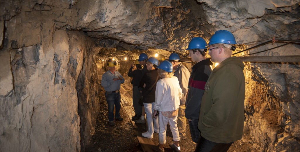 A tour group walking through a mine shaft.