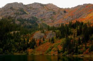 A forested mountain on the side of the lake.