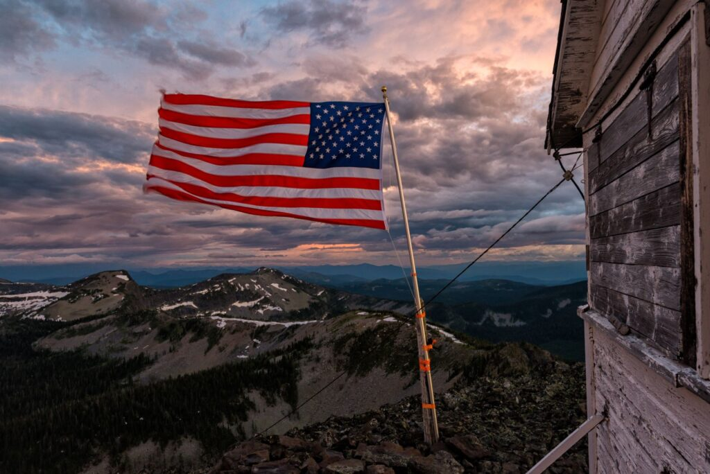 An american flag flying on top of a mountain.