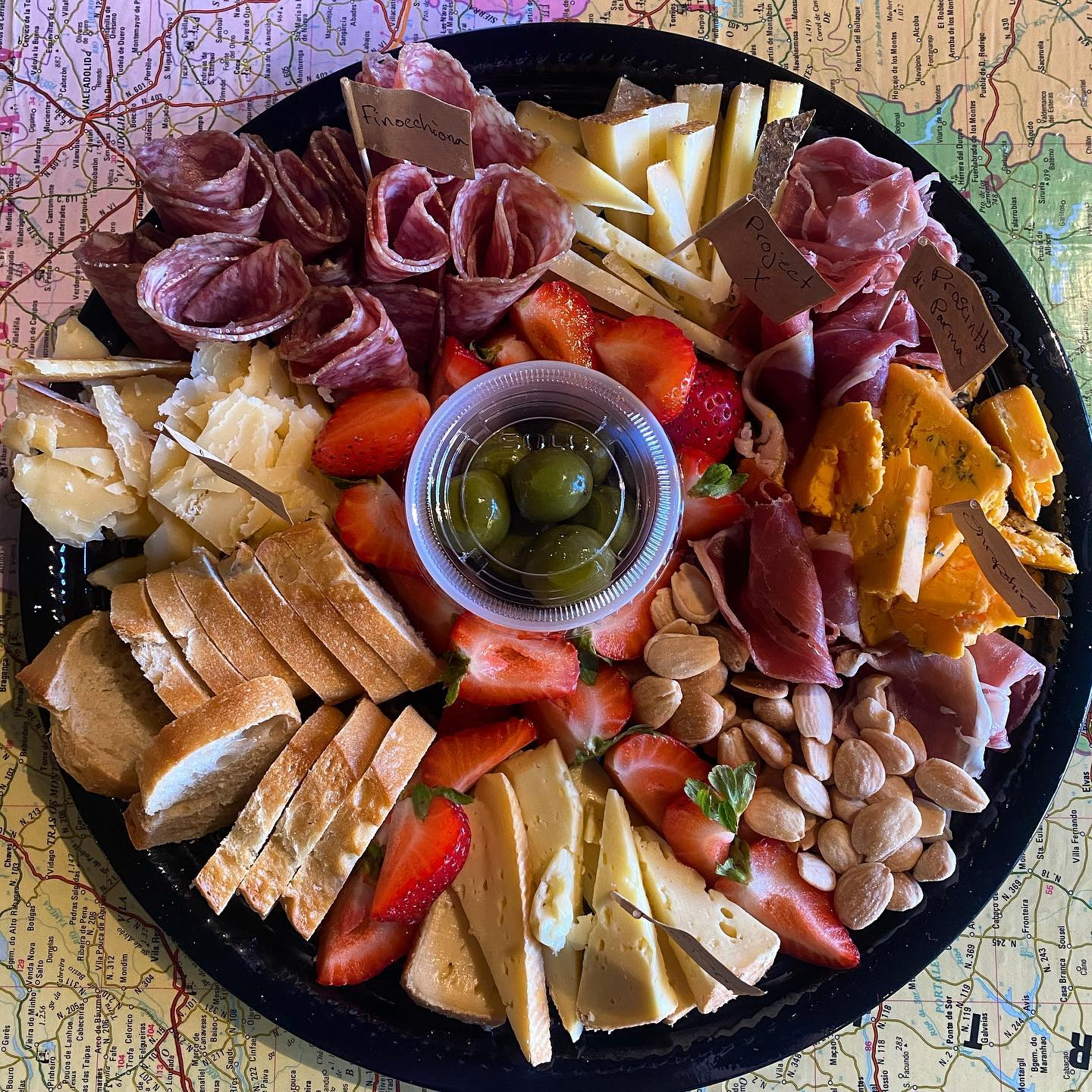 Charcuterie board of assorted cheeses, meats, nuts, berries and breads.
