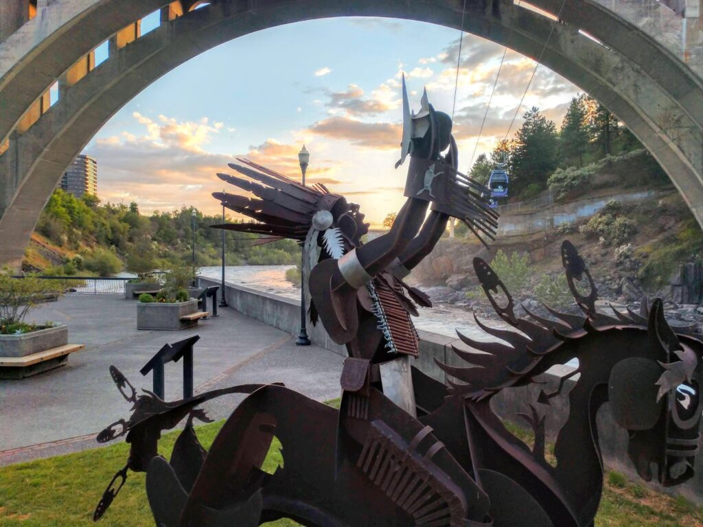 Metal sculture of Spokane Tribal member sitting atop horse and holding up a salmon. Huntington Park in downtown Spokane, with Spokane River alongside and Monroe Street Bridge above.