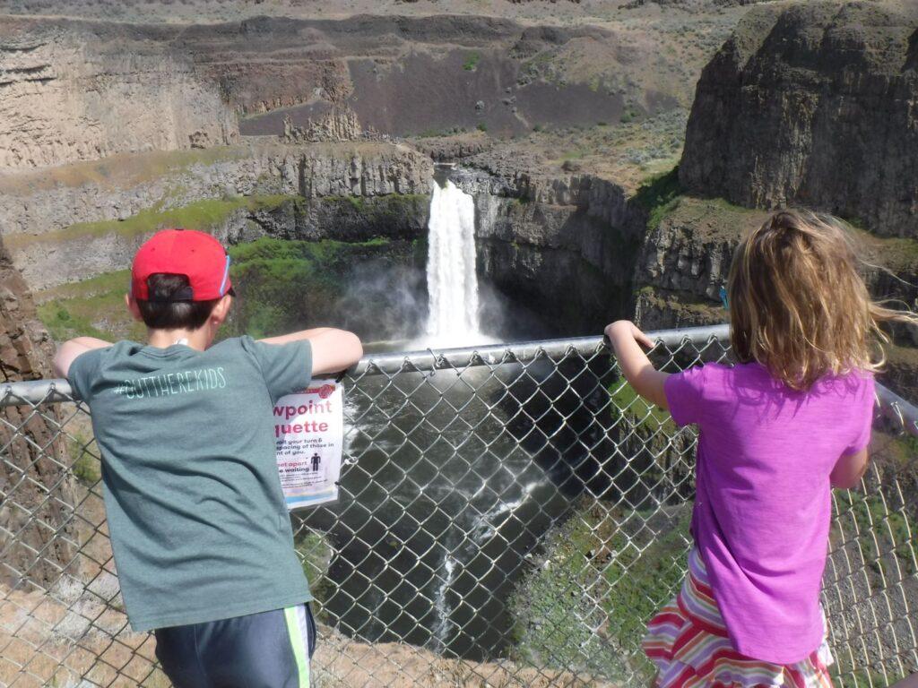 Two kids watching a waterfall.