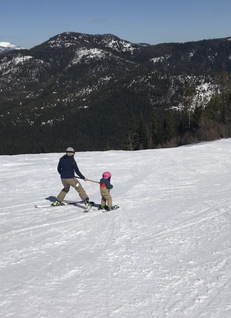 Mother teaching daughter to ski at 49 degrees north.