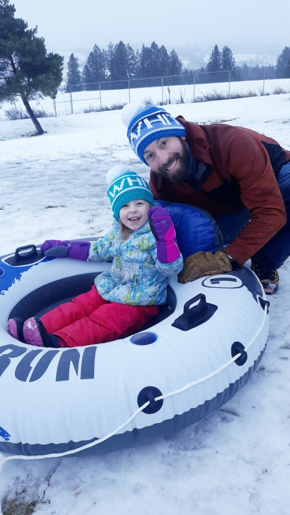 Father and daughter snow tubing.