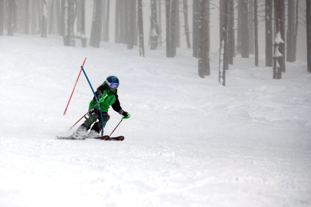 Ski racer turning around a slalom gate on race course.