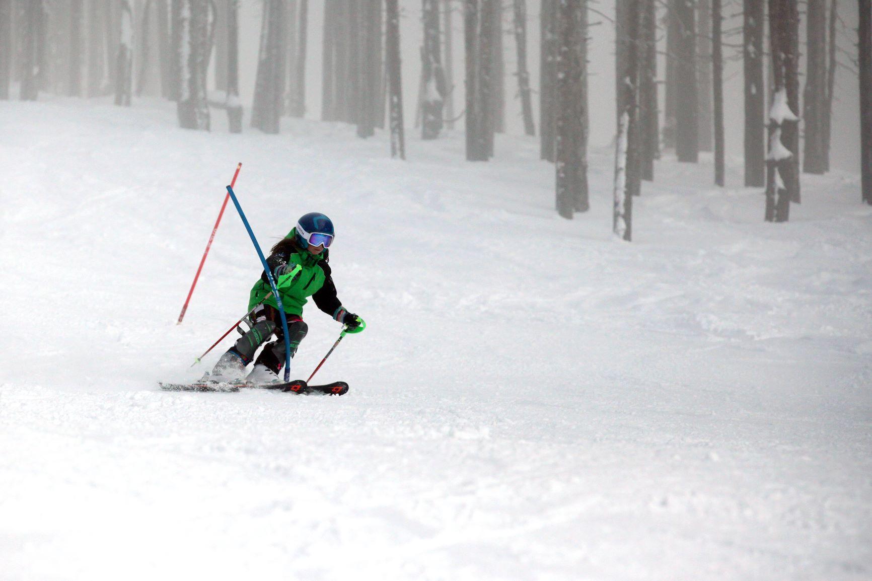 Ski racer turning around a slalom gate on race course.